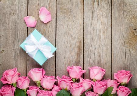 Roze rozen en Valentijnsdag geschenkdoos over houten tafel. Bovenaanzicht met een kopie ruimte Stockfoto
