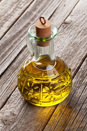 olive oil bottle: Olive oil bottle on wooden table Stock Photo