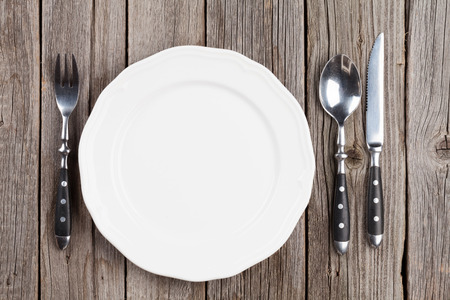 dining set: Empty plate and silverware on wooden table. Top view