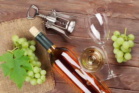 vid: Racimo de uvas, vino blanco y sacacorchos sobre fondo de madera