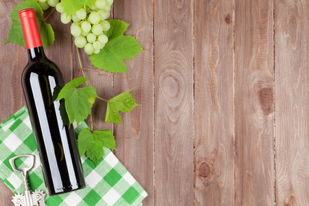 grapes wine: Bunch of grapes, red wine bottle and corkscrew on wooden table background with copy space