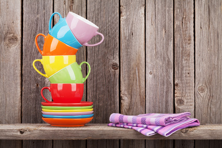 vintage kitchen: Colorful coffee cups on shelf against rustic wooden wall with copy space