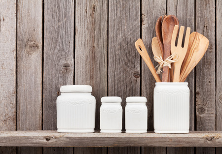 rustic kitchen: Kitchen cooking utensils on shelf against rustic wooden wall