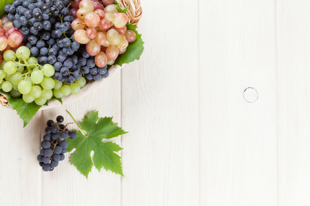 Bunch of red, purple and white grapes in basket on wooden table background with copy space