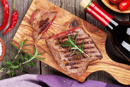 sal: Grilled beef steak with rosemary, salt and pepper and wine bottle on wooden table. Top view