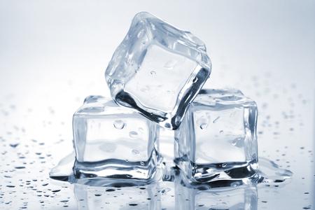 vasos de agua: Tres cubos de hielo fusión sobre mesa de vidrio  Foto de archivo