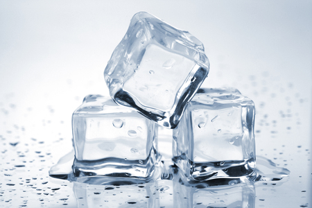 Three melting ice cubes on glass table Banque d'images