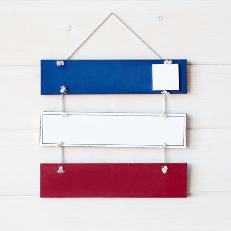 letreros: Tres carteles de colores en la pared de madera