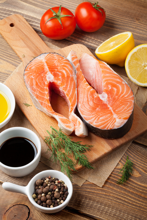 condiments: Salmon, spices and condiments on wooden table. Top view Stock Photo