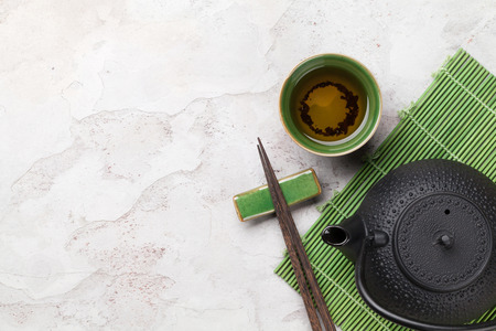 exotic food: Asian tea bowl and teapot over stone table. Top view with copy space Stock Photo