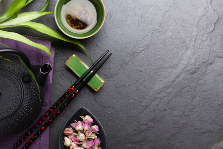 japanese green tea: Asian sushi chopsticks, rose tea and teapot over stone table. Top view with copy space