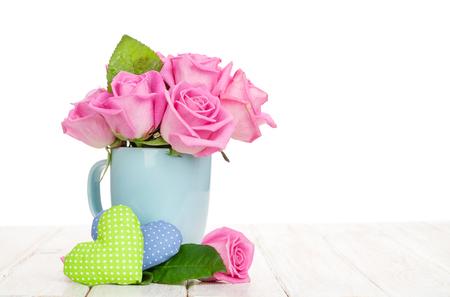 Valentijnsdag roze rozen boeket en handmaded speelgoed harten op witte houten tafel