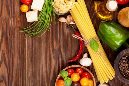 copies: Italian food cooking ingredients. Pasta, vegetables, spices. Top view with copy space