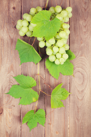 white grape: Bunch of white grapes with leaves on wooden background