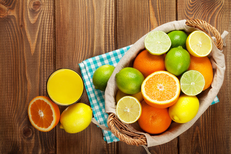citrus fruits: Citrus fruits and glass of juice. Oranges, limes and lemons. Top view over wood table background Stock Photo