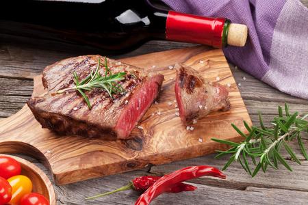 木製のテーブルにローズマリー、塩、こしょう、ワインのボトルと牛肉のグリル ステーキ