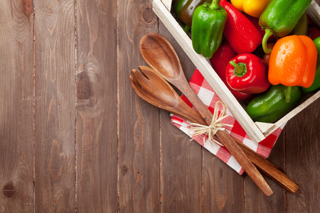 sweet food: Fresh colorful bell pepper box on wooden table. Top view with copy space