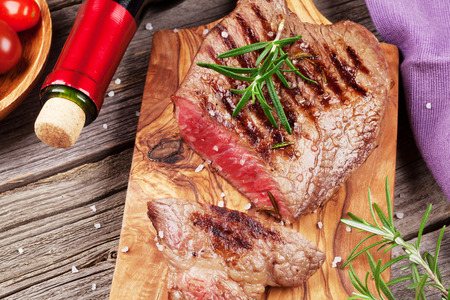 로즈마리, 소금 및 후추와 나무 테이블에 레드 와인 구운 된 쇠고기 스테이크