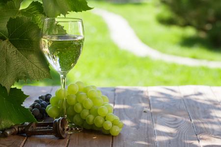bicchiere di vino bianco con l'uva bianca sul tavolo da giardino