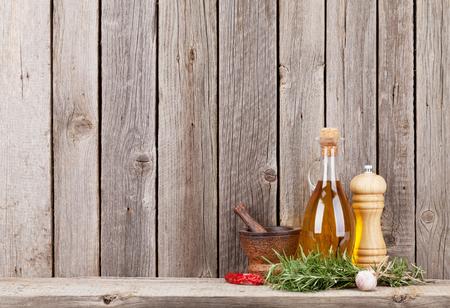 Keukengerei, kruiden en specerijen op de plank tegen de rustieke houten wand Stockfoto