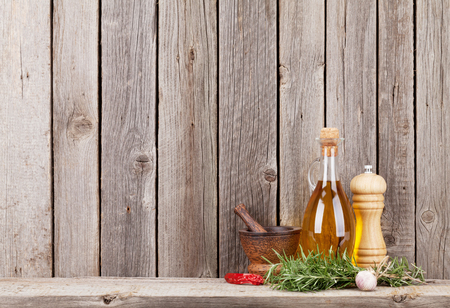 Kitchen utensils, herbs and spices on shelf against rustic wooden wall