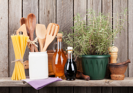 vintage kitchen: Kitchen utensils, herbs and spices on shelf against rustic wooden wall