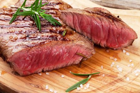 Gegrilde biefstuk met rozemarijn, zout en peper op snijplank