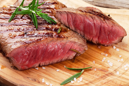 cut and blood: Grilled beef steak with rosemary, salt and pepper on cutting board Stock Photo