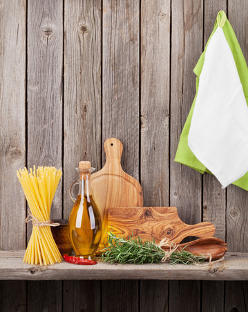 utensils: Kitchen utensils, herbs and spices on shelf against rustic wooden wall