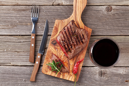 juicy: Grilled beef steak with rosemary, salt and pepper and wine on wooden table. Top view