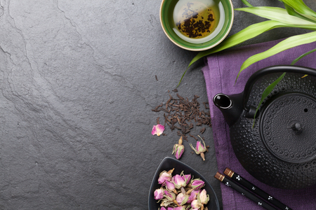 Asian sushi chopsticks, rose tea and teapot over stone table. Top view with copy space