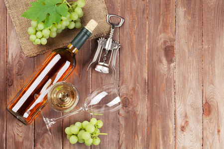 Bunch of grapes, white wine and corkscrew on wooden table background. Top view with copy space
