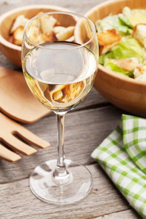 lunch: ensalada C�sar fresca y saludable y el vino blanco de mesa de madera Foto de archivo