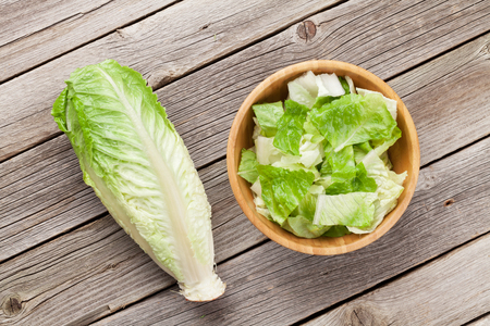 food dressing: Fresh healthy romaine lettuce salad on wooden table. Top view
