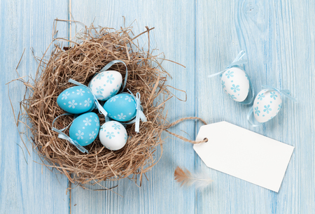 quail nest: Easter card with eggs in nest on blue wooden table. Top view with copy space