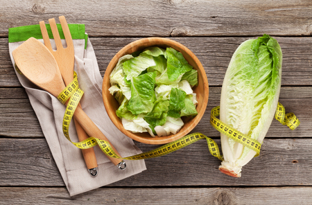 romaine: Fresh healthy romaine lettuce salad cooking on wooden table