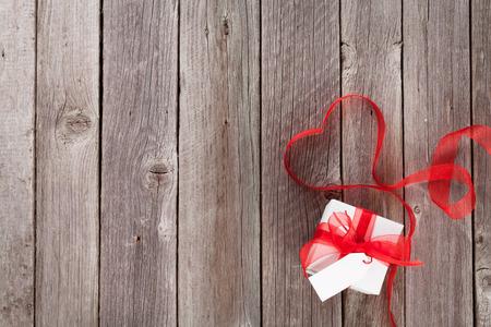 trompo de madera: coraz�n de la cinta D�a de San Valent�n y caja de regalo sobre la mesa de madera. Vista superior con espacio de copia