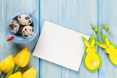 Easter greeting card with eggs and yellow tulips over blue wooden table. Top view with copy space