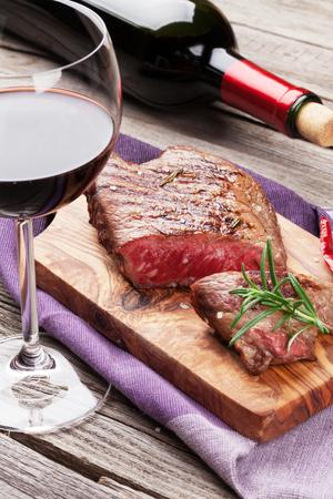 Gegrilltes Rindersteak mit Rosmarin, Salz und Pfeffer und Rotwein auf Holztisch Lizenzfreie Bilder