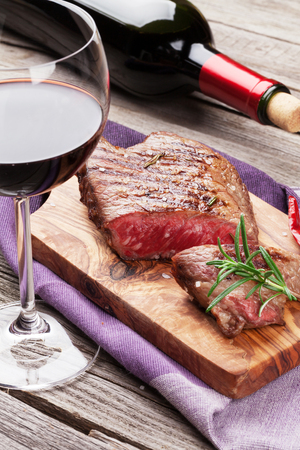 glass bottle: Grilled beef steak with rosemary, salt and pepper and red wine on wooden table Stock Photo