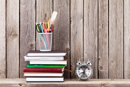 pencil: Wooden shelf with books and supplies in front of wooden wall. View with copy space Stock Photo