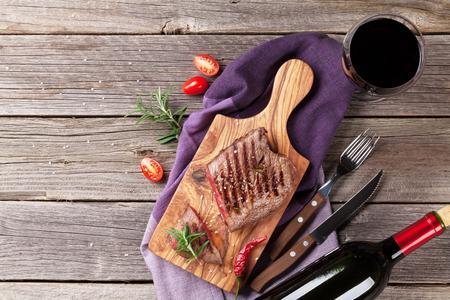 copa de vino: filete de carne a la parrilla con romero, sal y pimienta y vino tinto en la mesa de madera. Vista superior con espacio de copia
