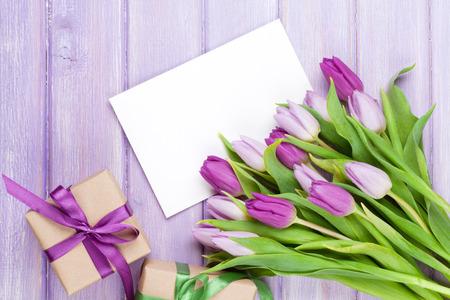 morado: Ramo del tulipán púrpura, tarjetas de felicitación y cajas de regalo en blanco. Vista superior sobre la mesa de madera