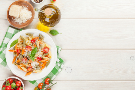 italian: Colorful penne pasta with tomatoes and basil on wooden table. Top view with copy space
