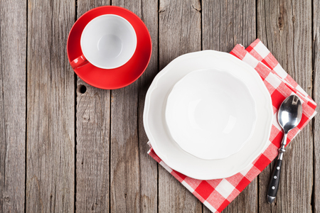 Empty plate, cup and spoon on wooden table. Top view with copy space