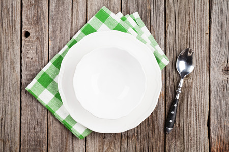 Empty plate and spoon on wooden table. Top view