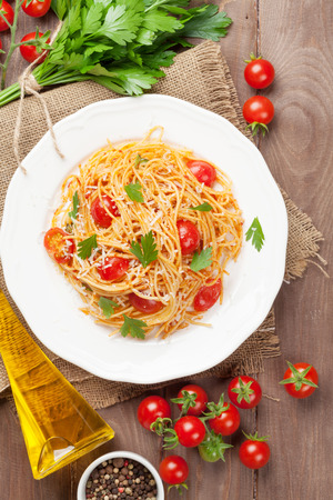 Spaghetti pasta with tomatoes and parsley on wooden table. Top view Stock fotó