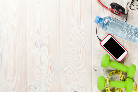 Dumbbells, water bottle, smartphone, headphones and tape measure. Top view with copy space