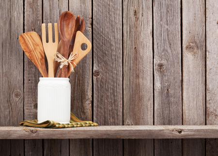 rustic kitchen: Kitchen utensils on shelf against rustic wooden wall