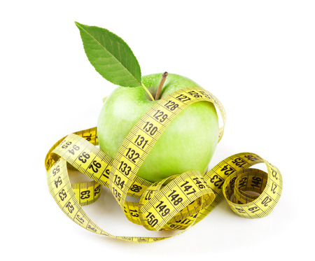 Diet concept. Apple and tape measure. Isolated on white background